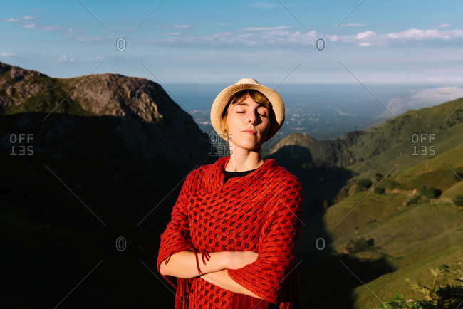 Tranquil female traveler standing on hill and enjoying sun during holiday on background of amazing highland valley