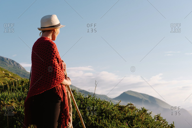 Side view of unrecognizable tranquil female traveler standing on hill and enjoying sun during holiday on background of amazing highland valley