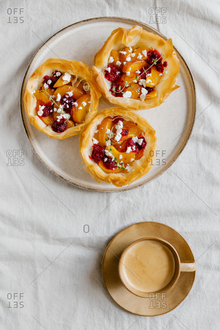 Top view of yummy tarts made of filo dough and filled with sliced fruits served with cup of aromatic coffee with milk