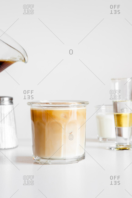 Delicious iced coffee latte served in glass cup on white table with cup of milk and glassware