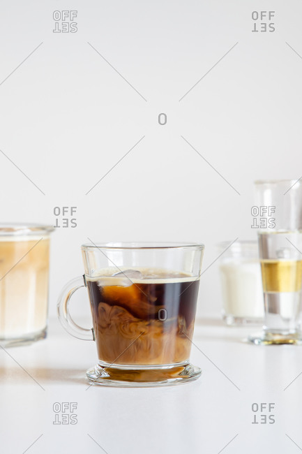 Fresh aromatic iced coffee with milk served in glass mug on table decorated with flowers