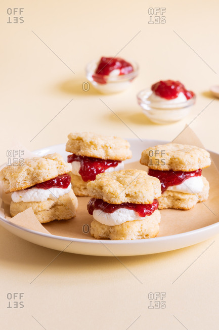 Appetizing homemade sweet scones with berry jam and whipped cream served on plate