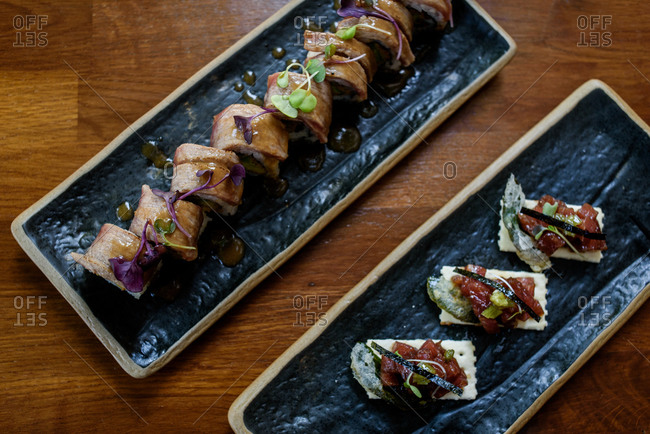 Top view of assorted delicious rolls with herbs served on plates in restaurant