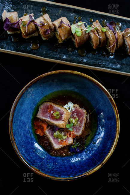 From above of bowl with seared ahi tuna garnished with caviar and herbs and placed on wooden table in cafe