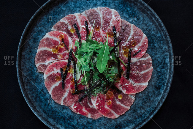 From above of slices of carpaccio slices on plate garnished with green herbs in cafe on black background