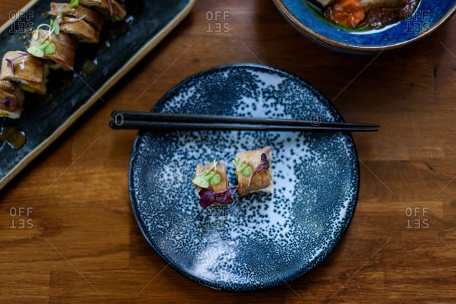 From above of appetizing rolls with rice and salmon garnished with fresh herbs and placed on plate with bamboo chopsticks in restaurant