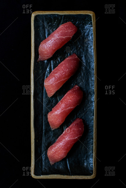 From above of delicious salmon sushi served on plate with chopstick in restaurant on black background