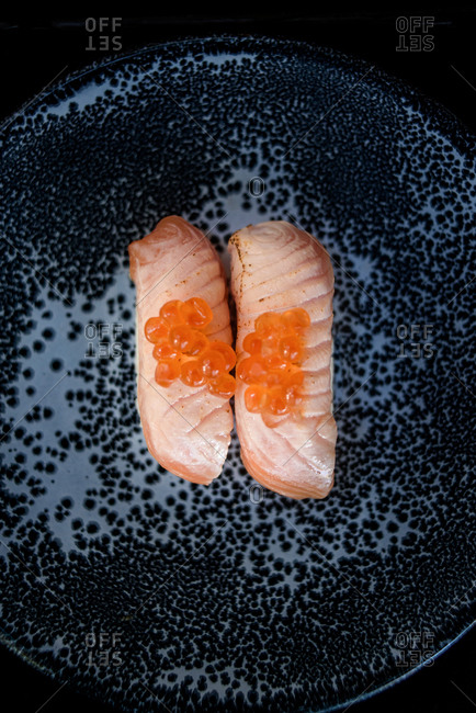 Top view of appetizing fish sushi garnished with caviar and served on plate in restaurant
