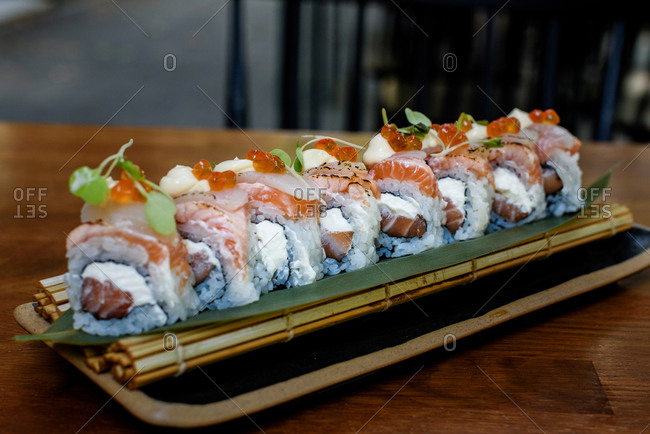 From above of tasty rolls with rice and fish garnished with caviar and cheese sauce and placed on table in luxury restaurant