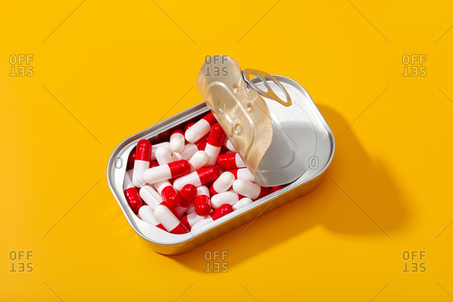From above of metal container with pile of capsules placed on yellow table in studio