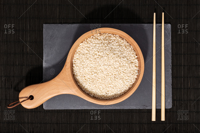 Top view of wooden bowl with raw rice and bamboo chopsticks placed on black slate board in restaurant