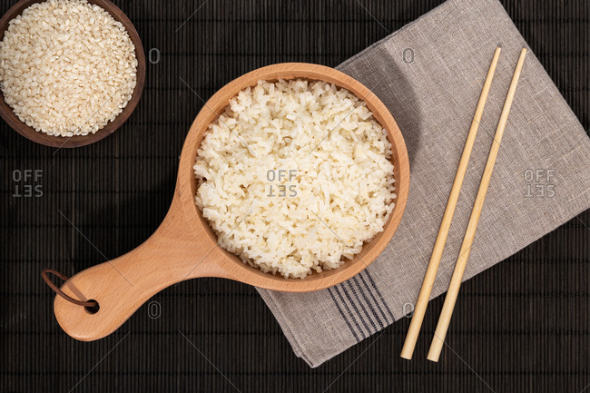 Top view of wooden bowl with cooked rice and a bowl with raw rice and bamboo chopsticks placed on black slate board in restaurant