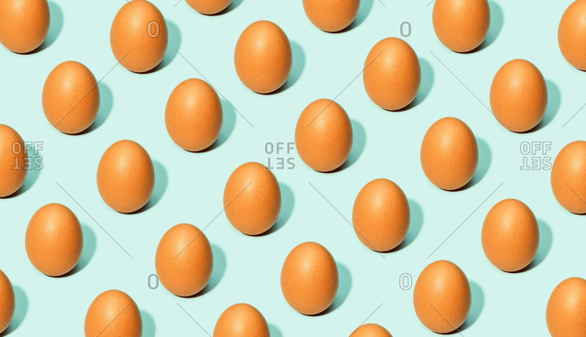 Seamless background of brown eggs placed in rows on white table in studio