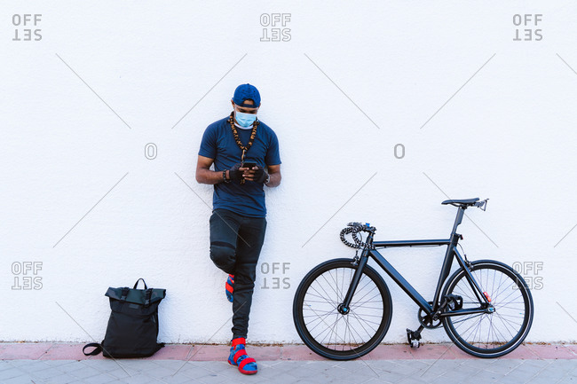 Full body young African American hip hop guy in medical mask messaging on mobile phone while standing near backpack and bicycle near white stone wall on urban street