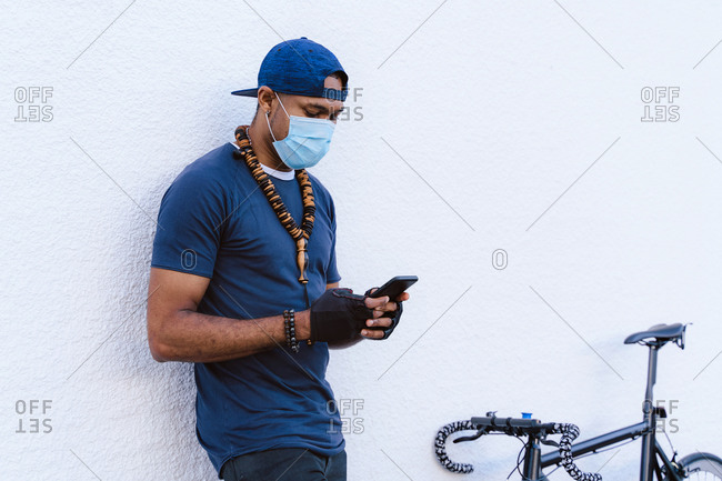 Young African American hip hop guy in medical mask messaging on mobile phone while standing near backpack and bicycle near white stone wall on urban street