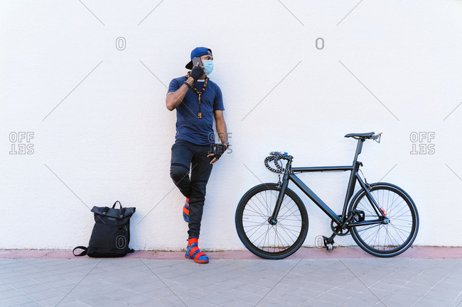 Full body young African American man in medical mask speaking on mobile phone while standing near backpack and bicycle near white stone wall on urban street