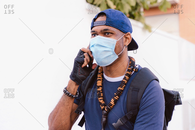Young African American male in stylish outfit with accessories and medical mask talking on smartphone while riding bicycle on street