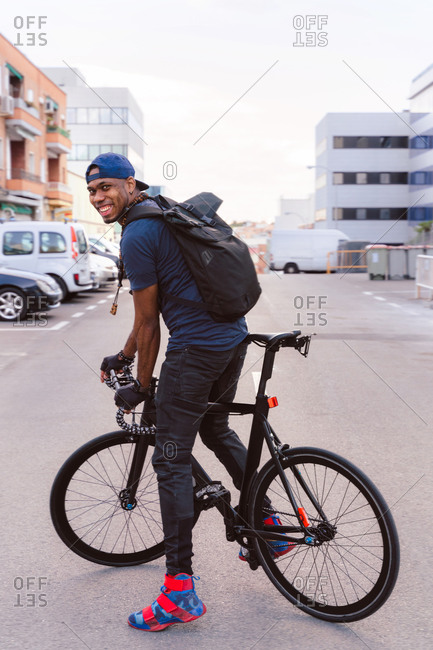 Full body side view of positive young African American guy in stylish wear with backpack riding bicycle on urban street