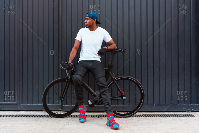 Full body of serious young African American man in casual street style wear and trendy boots standing with bike against gray wall on street and looking away