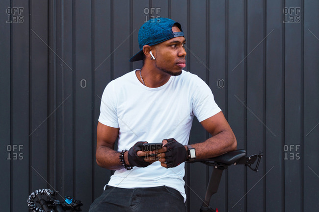 Positive young African American male biker with bracelets, cap and using earbuds while choosing playlist on smartphone standing with bicycle against gray metal wall
