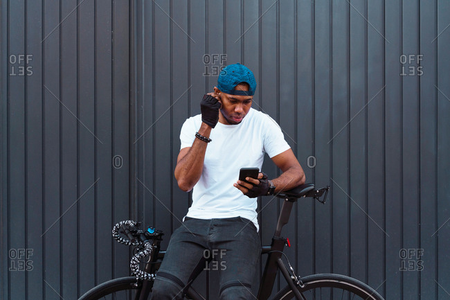Positive young African American male biker with bracelets and cap adjusting earbuds and choosing playlist on smartphone while standing with bicycle against gray metal wall