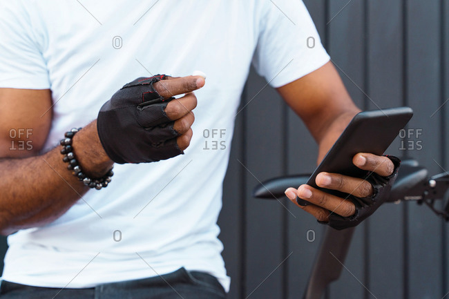 Cropped unrecognizable African American male biker with bracelets and gloves holding earbuds while choosing playlist on smartphone standing with bicycle against gray metal wall