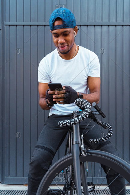 From below positive young African American male biker with bracelets and cap using earbuds and choosing playlist on smartphone while standing sitting in bicycle against gray metal wall