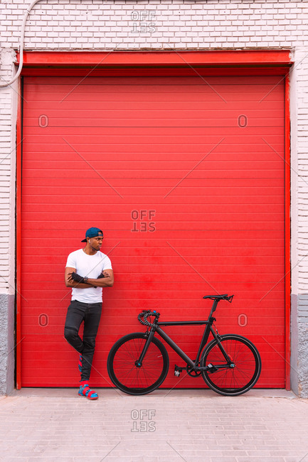 Full body of confident young African American male in street style clothing with bicycle leaning back on red shuttered door of urban building