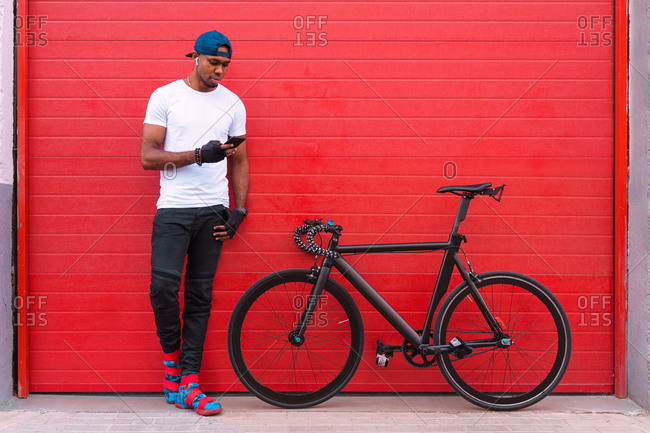 Full body of young African American man in trendy outfit and cap with earbuds standing near bike and sending audio message on mobile phone while resting against red wall on street