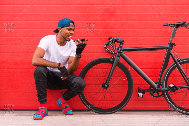 Full body of cheerful young African American guy in trendy outfit and cap with earbuds sitting near bike and sending audio message on mobile phone while resting against red wall on street