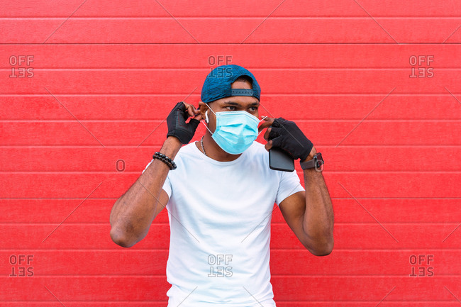 Black male in gloves and bracelet putting on disposable medical mask while standing against red wall on street