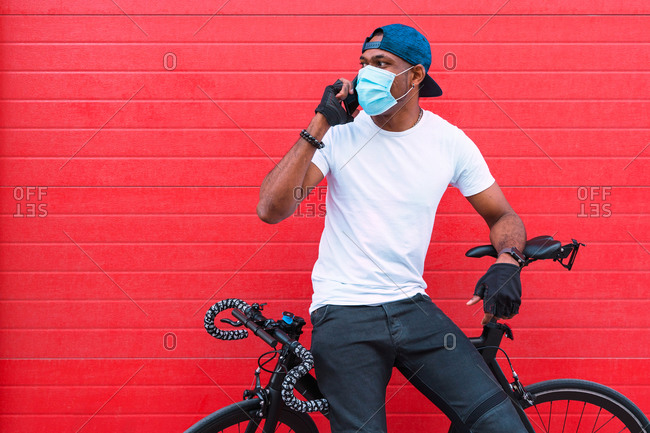 Black male in gloves and bracelet wearing a disposable medical mask while speaking on the mobile phone standing against red wall on street looking away