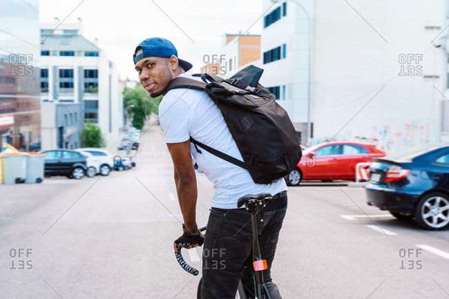 Side view of positive young African American guy in stylish wear with backpack riding bicycle on urban street looking at camera