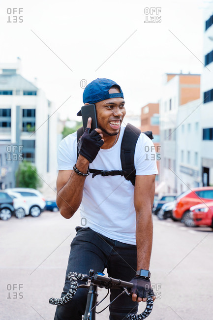 Happy young African American male biker in casual outfit talking on mobile phone while riding bicycle on city street