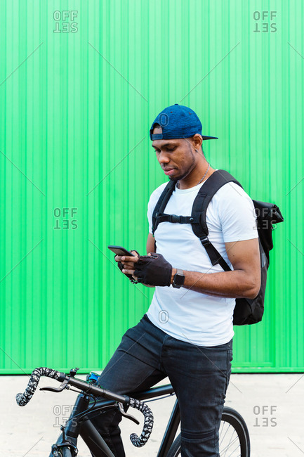 Positive young African American male biker with cap and backpack using smartphone while sitting on bicycle against green wall