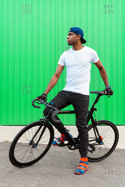 Happy young African American man in casual street style standing sitting on bike against green wall on street and looking away