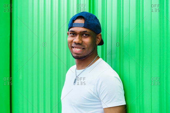 Side view of happy young African American hipster male in cap with metal chain looking at camera while standing against green wall on city street