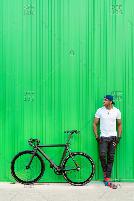 Young African American man in casual street style standing near bike against green wall on the street and looking away