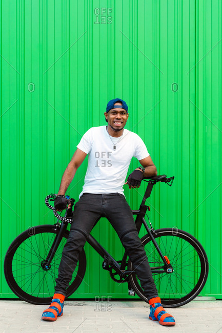Full body of cheerful young African American man in casual street style wear and trendy shoes sitting on bike against green wall on street and looking away