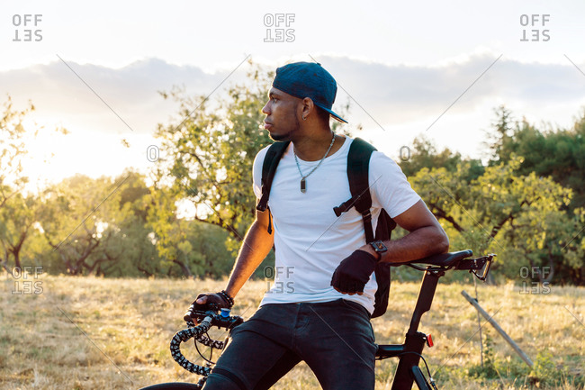 Calm young African American male in casual wear and cap with backpack leaning on bicycle and looking away while standing on green meadow against blurred hills in sunny summer day