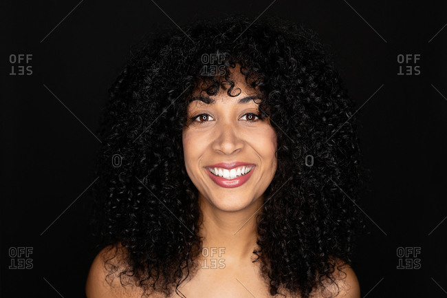 Young beautiful mixed race female with curly hair looking at camera smiling on black background