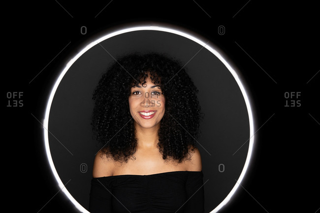 Happy African American woman with curly hair standing in a light circle frame looking at camera in studio