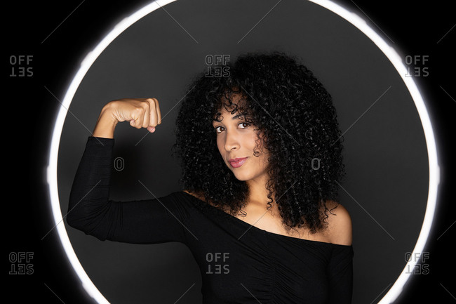 Powerful woman doing an arm lifting weights sign as a concept of black woman strength and power.