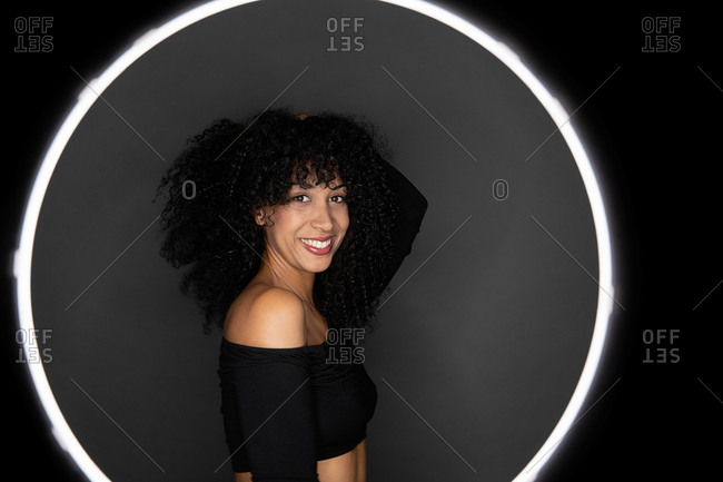 Side view of cheerful African American woman with curly hair standing in a light circle frame looking at camera in studio
