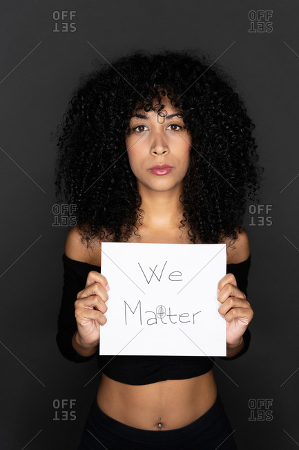 Portrait of a black female with curly hair holding a whiteboard with the peaceful message black lives matter looking at camera on black background