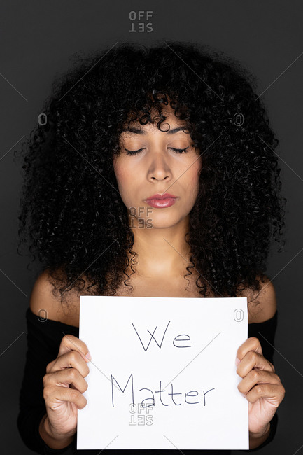 Portrait of a black female with curly hair holding a whiteboard with the peaceful message black lives matter with eyes closed on black background
