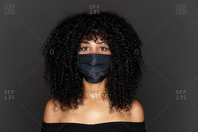 Ethnic young woman covering her mouth with medical face mask against coronavirus pandemic disease. Healthcare and contagious prevention concept.