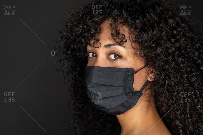 Side view of ethnic young woman covering her mouth with medical face mask against coronavirus pandemic disease. Healthcare and contagious prevention concept.