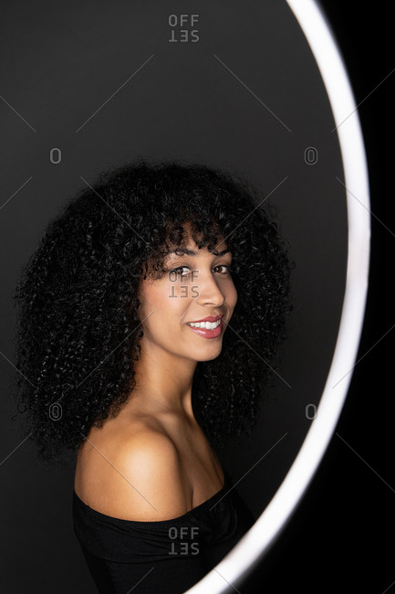 Side view of happy African American woman with curly hair standing in a light circle frame looking at camera