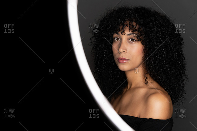 Side view of thoughtful African American woman with curly hair standing in a light circle frame looking at camera